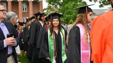 Students walk down the aisle during Commencement